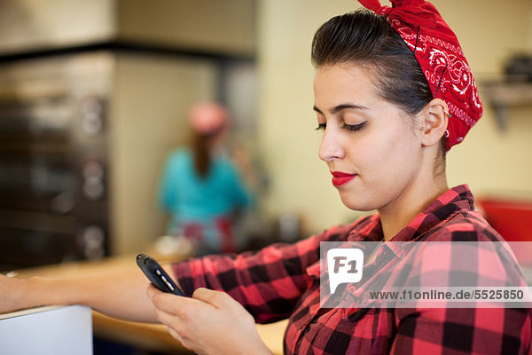 Young woman using cellphone in bakery