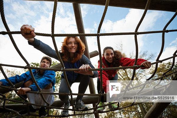 Junge Freunde beim Klettern in der Sturmkursausrüstung