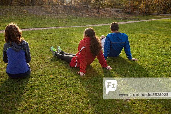 Rückansicht sitzend Freundschaft jung 3 Gras