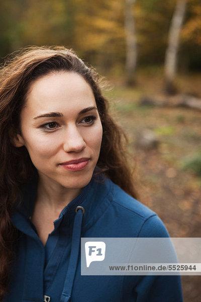 Junge Frau im Wald Lächeln  wegschauen