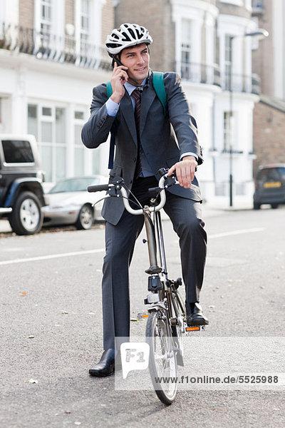 Mitte Erwachsenen Geschäftsmann mit Handy auf Fahrrad