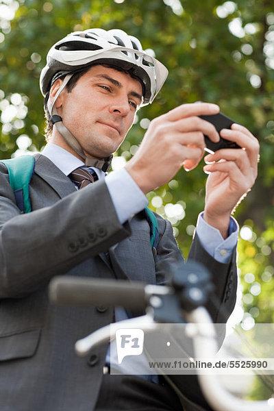 Mitte Erwachsenen Geschäftsmann mit Mobiltelefon  um Text auf dem Fahrrad
