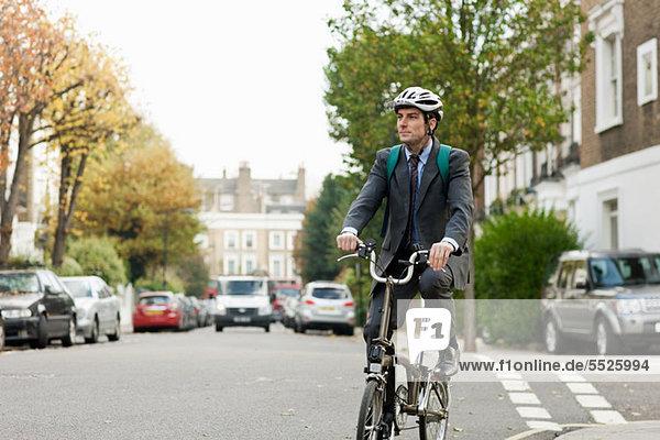 Mittlerer Erwachsener Geschäftsmann  der auf der Straße Fahrrad fährt
