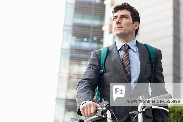Mitte Erwachsenen Geschäftsmann mit Fahrrad in der Stadt