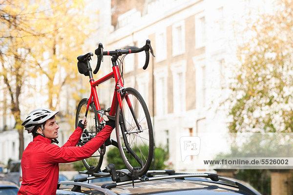 Mittlerer Erwachsener Mann  der das Fahrrad auf den Autodachträger hebt