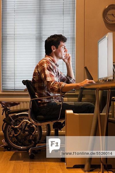 Mittlerer Erwachsener Mann mit Heimcomputer am Schreibtisch