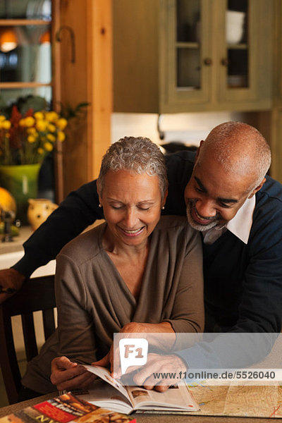 Mature couple looking through book together