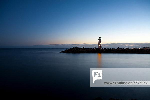 Leuchtturm mit Blick auf ruhiges Wasser in der Abenddämmerung