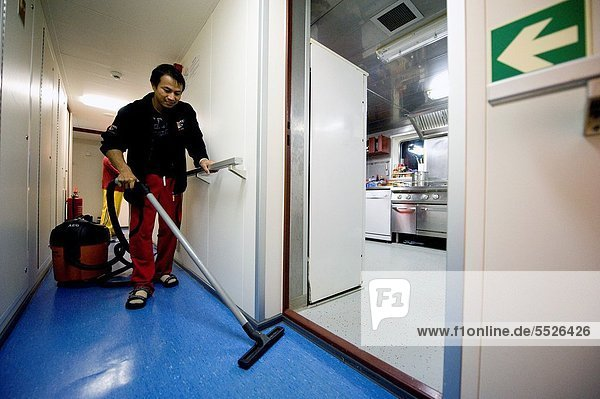 An Indonesian seaman or sailor on the container-vessel MV Flintercape  during a journey from Rotterdam  Netherlands  to Sundsvall  Sweden. The man is an ´Able Seaman´  who generally works on deck  and now cleans the interior of the wheelhouse.