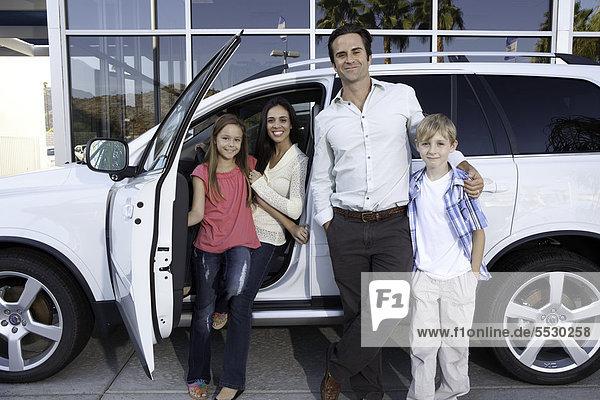Glückliche Familie neben dem weißen Auto