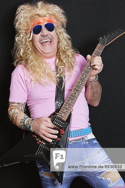 Cheerful senior man wearing sunglasses and playing guitar