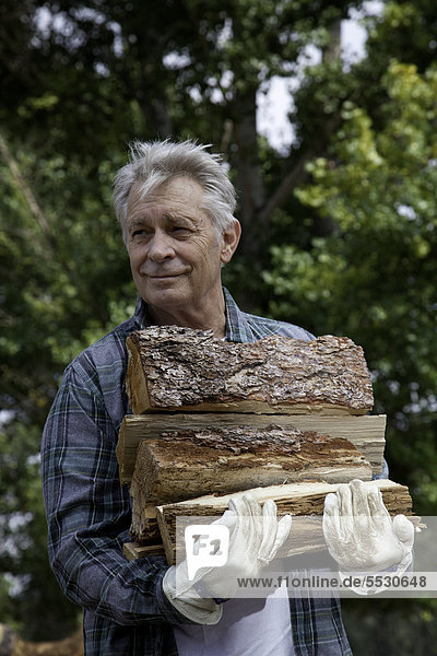 Senior man carrying firewood
