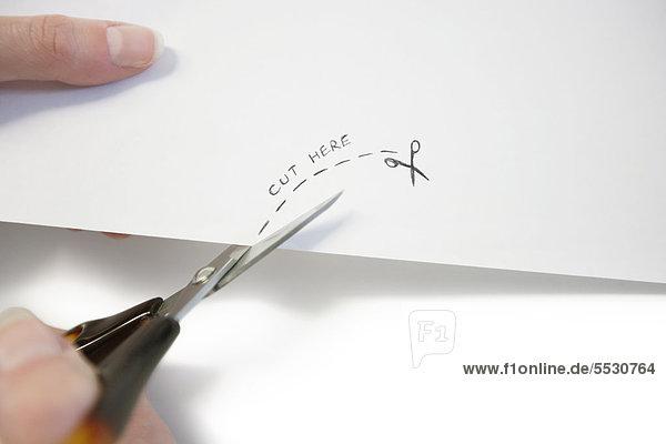 Hand mit Schere Papier schneiden