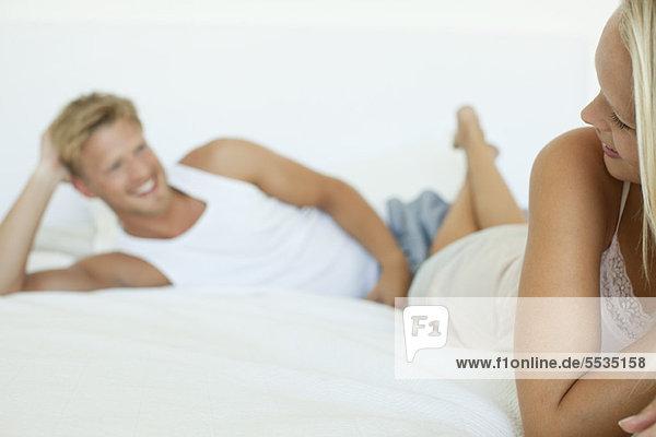 Paar auf dem Bett liegend  Frau über die Schulter lächelnd Mann