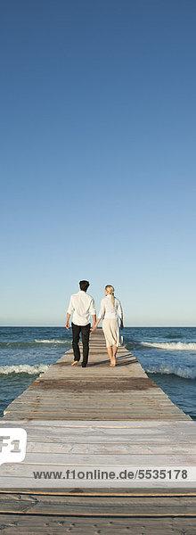Paar beim Gehen auf dem Pier mit den Händen  Rückansicht