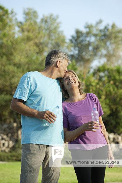 Älterer Mann,  der die Stirn seiner Frau küsst.