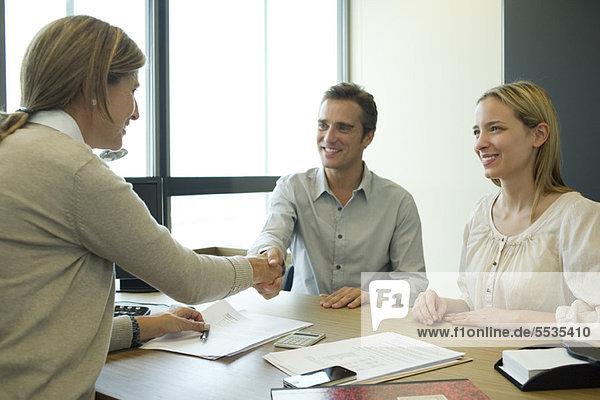 Paar schüttelt sich die Hand mit Geschäftsfrau im Büro