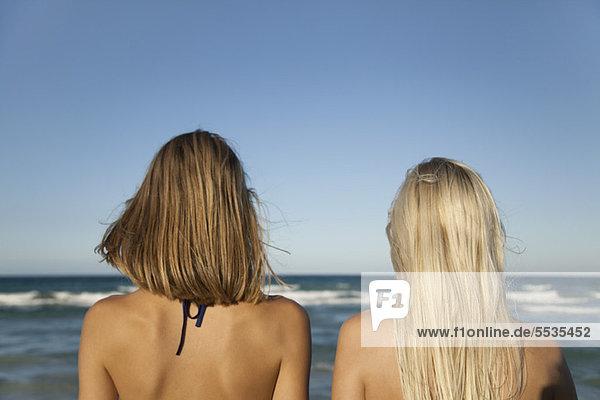 Frauen Seite an Seite am Strand  Blick aufs Meer  Rückansicht