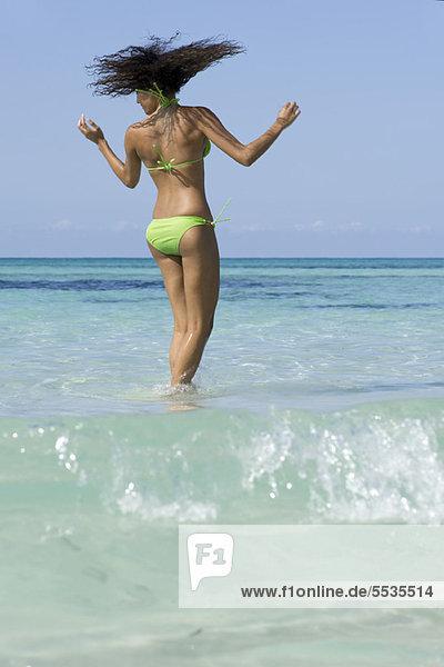 Frau im Bikini im Wasser stehend  Kopf schüttelnd