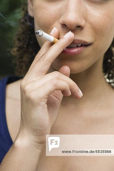 Junge Frau raucht Zigarette  abgeschnitten