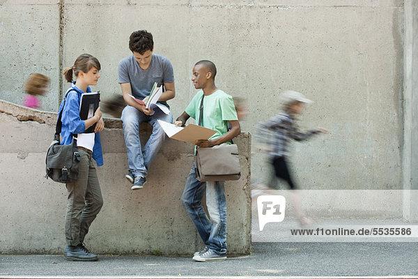 Freunde diskutieren gemeinsam über Hausaufgaben