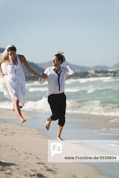 Braut und Bräutigam laufen Hand in Hand am Strand.