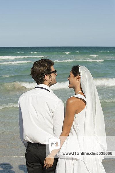 Braut und Bräutigam am Strand stehend  Blick auf die Aussicht