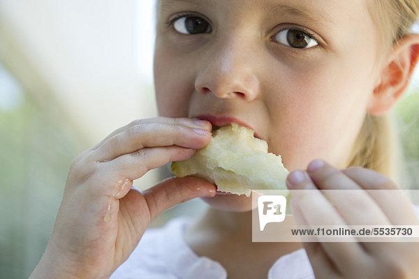 Little girl eatiing apple