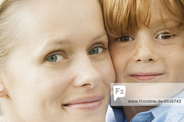 Mother and young son cheek to cheek  portrait
