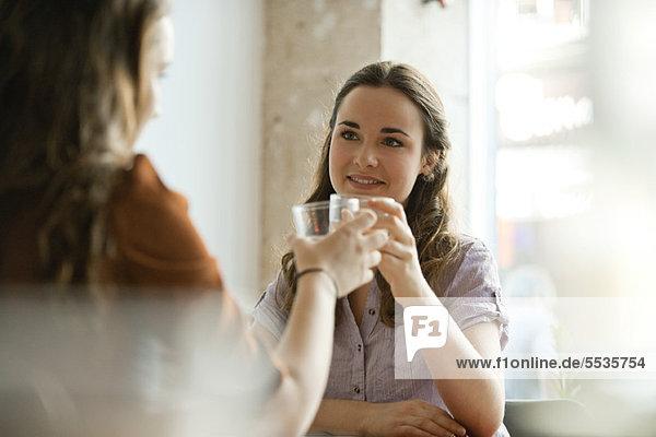 Junge Frauen  die Gläser erheben