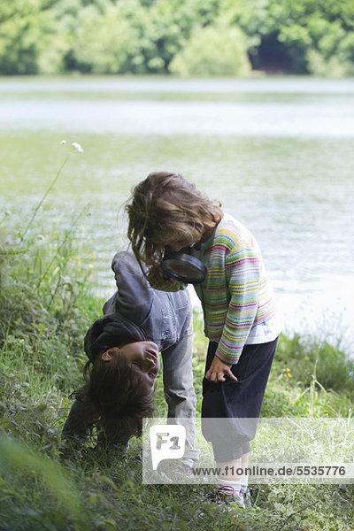Kinder beim Spielen mit der Lupe im Freien