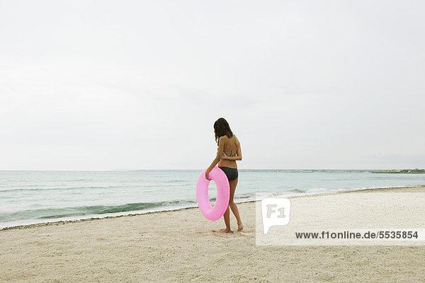 Frau steht am Strand  hält aufblasbaren Ring  Rückansicht