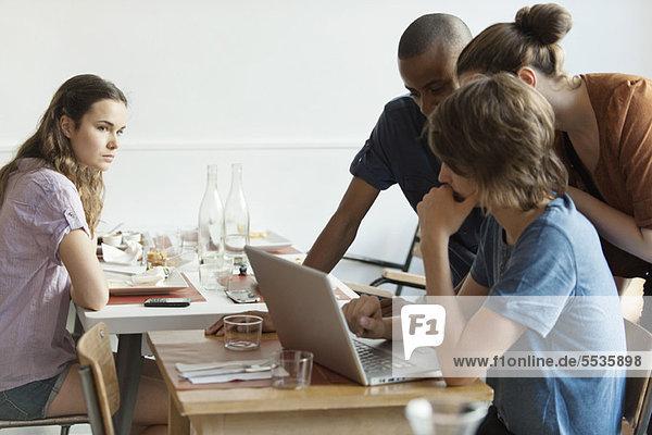 Junge Frau beobachtet Freunde mit Laptop-Computer