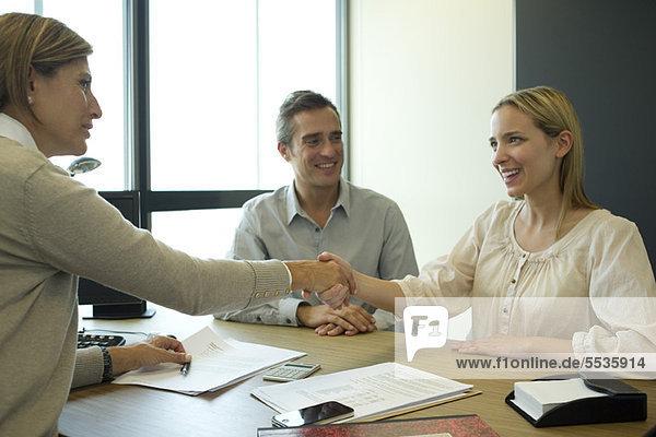 Geschäftsfrau beim Händeschütteln mit dem Kunden im Büro