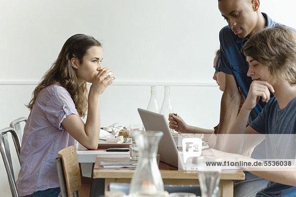 Freunde im Restaurant  Frau beim Essen  Mann am Laptop