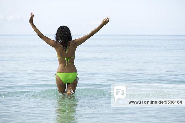 Frau im Bikini stehend im Meer mit ausgestreckten Armen  Rückansicht