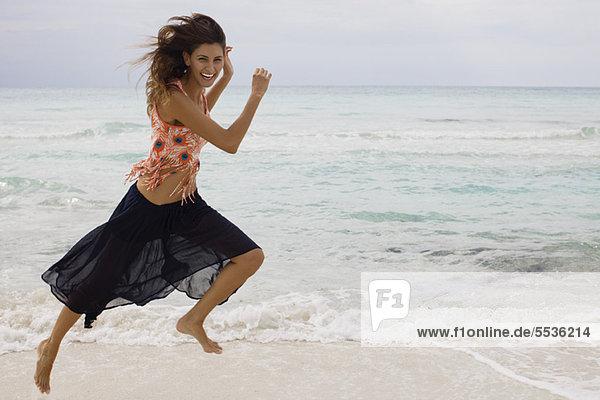 Frau  die am Strand läuft