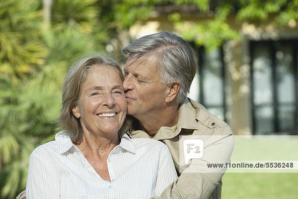 Senior Mann  der seine Frau auf die Wange küsst.