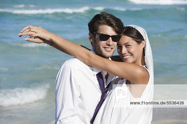 Braut und Bräutigam umarmend am Strand  Portrait