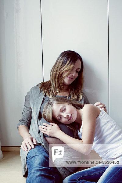 Tochter hört auf den Bauch der schwangeren Mutter  Porträt