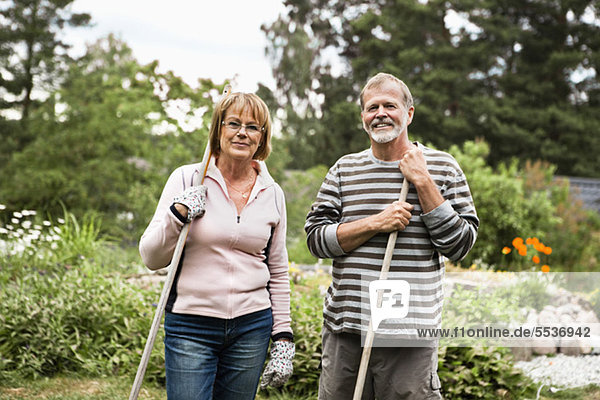 Porträt von lächelnden aktiven Senioren mit Rechen