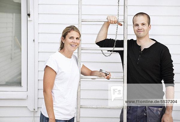 Glücklicher Mann und Frau stehen an der Leiter