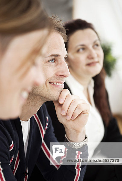 Side view of business colleagues in seminar with focus on man smiling