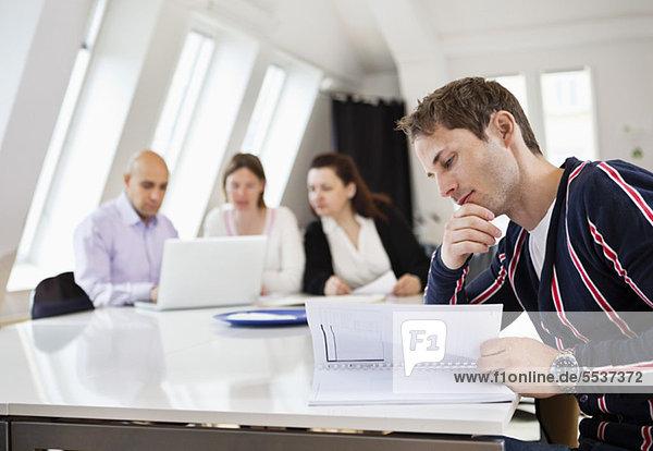 Mann beim Lesen von Dokumenten mit Geschäftskollegen im Sitzungssaal
