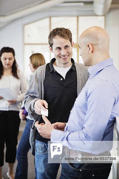 Geschäftsmann überreicht eine Visitenkarte an seine Kollegen mit Menschen im Hintergrund