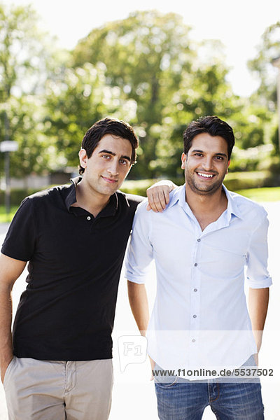 Portrait of young friends standing outdoors with hand on shoulder