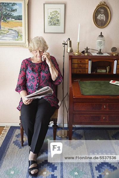 Ältere Frau sitzt auf dem Stuhl und telefoniert beim Zeitungslesen.