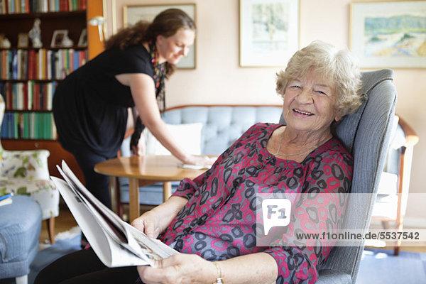 Porträt einer lächelnden Seniorin mit einer mittleren erwachsenen Frau im Hintergrund