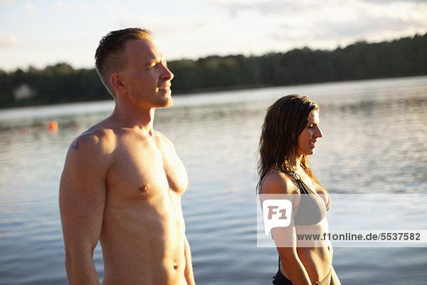 Paar schaut weg mit Wasser im Hintergrund