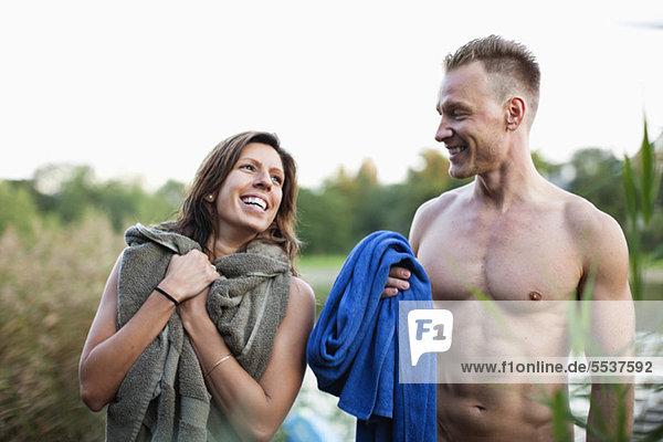 Fröhliches Paar mit Handtuch am Strand